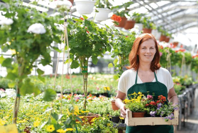 Gärtnerin trägt einen Korb mit Blumen
