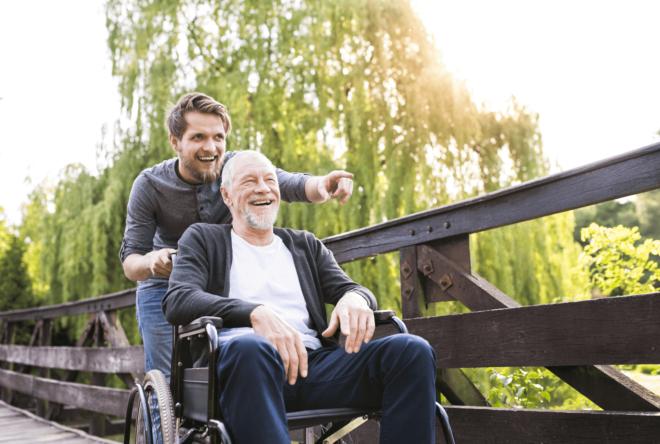 junger Mann schiebt einen älteren Mann im Rollstuhl