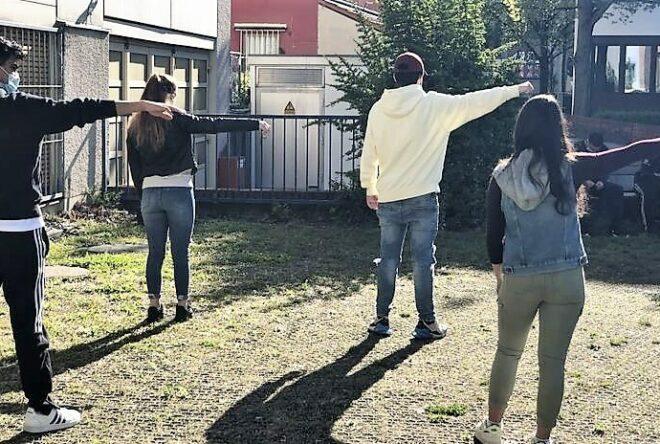 vier Schüler strecken ihren Arm zur Seite
